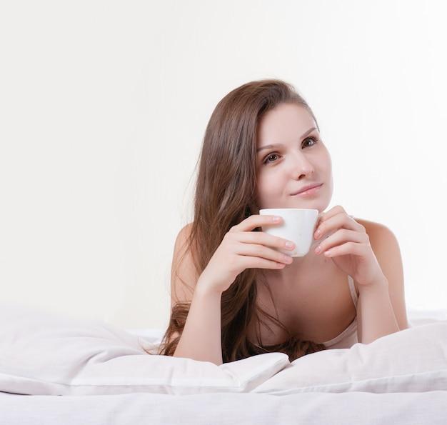 Femme sur son lit en souriant tout en tenant une tasse de café