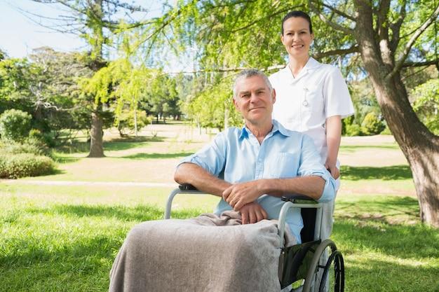 Femme avec son père assis dans une chaise roulante au parc