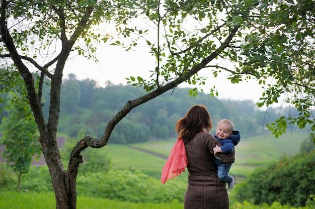 Femme avec son petit bébé marchant dans le parc de l'été