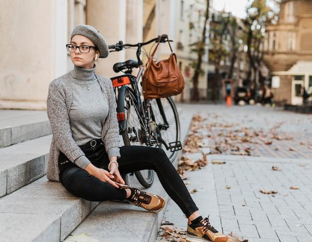 Femme et son vélo assis sur les escaliers en face du bâtiment