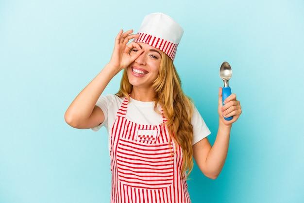 Femme de sorbetière caucasienne tenant une boule de crème glacée isolée sur fond bleu excité en gardant le geste ok sur les yeux.