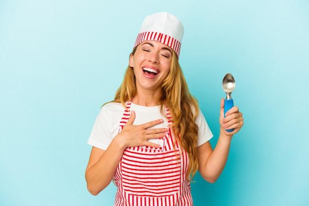 Une femme de sorbetière caucasienne tenant une boule de crème glacée isolée sur fond bleu rit fort en gardant la main sur la poitrine.