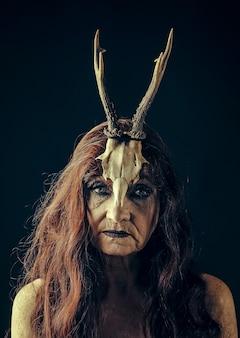 Femme de sorcière âgée en robe sombre sur fond noir. mamie epifania, shaman.