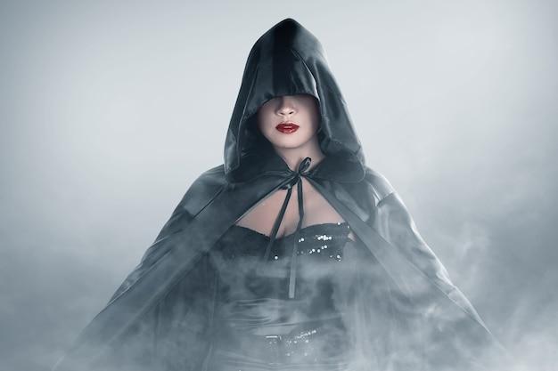 Femme sorcière asiatique avec un manteau debout dans le brouillard