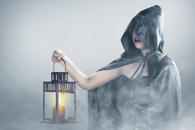 Femme sorcière asiatique avec un manteau tenant une lanterne debout dans le brouillard