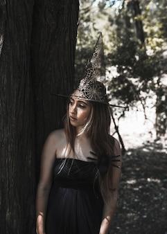 Femme, sorcière, chapeau, debout, arbre, regarder, loin