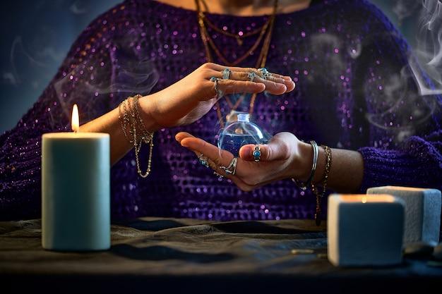 Femme sorcière fantastique utilisant une bouteille de potion d'élixir magique enchanteur pour le sort d'amour et la sorcellerie. illustration magique et alchimie