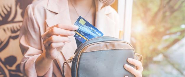 Une femme sort une carte de crédit de sa poche pour faire un achat. pour la bannière web.