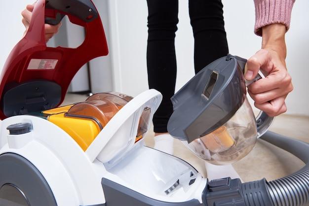 Femme sort le conteneur de poussière de l'aspirateur