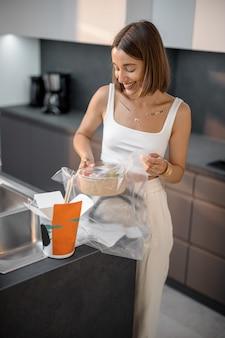 Une femme sort de l'emballage de la nourriture dans la cuisine