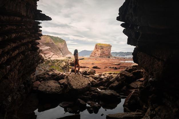 Femme sortant d'une grotte sur la côte basque