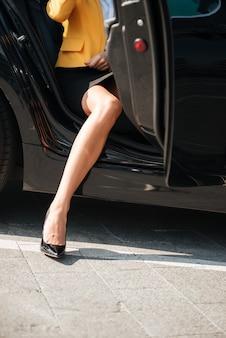 Femme sortant de sa voiture avec des chaussures à talons hauts