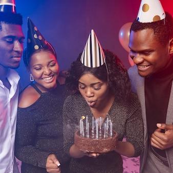 Femme soufflant des bougies sur son gâteau joyeux anniversaire
