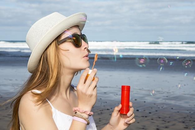 Femme soufflant des bulles au bord de la mer