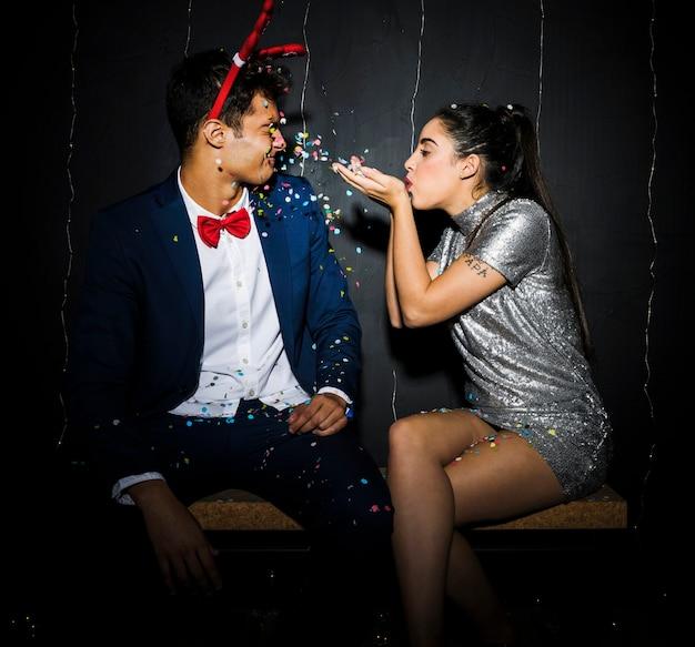 Femme soufflant des confettis sur l'homme avec bandeau en bois de cerf