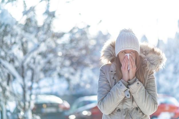 Femme soufflant dans un tissu dans un hiver froid avec une montagne enneigée en arrière-plan