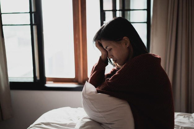 Femme souffrant de dépression assise sur le lit dans la chambre