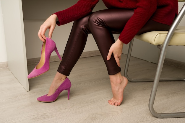 Femme souffrant de douleurs aux jambes au bureau. elle a frotté de terribles callosités causées par des chaussures à talons hauts inconfortables