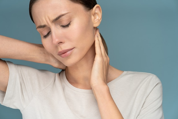 Femme souffrant de douleurs chroniques au cou, masse doucement avec les mains, se sentant fatiguée