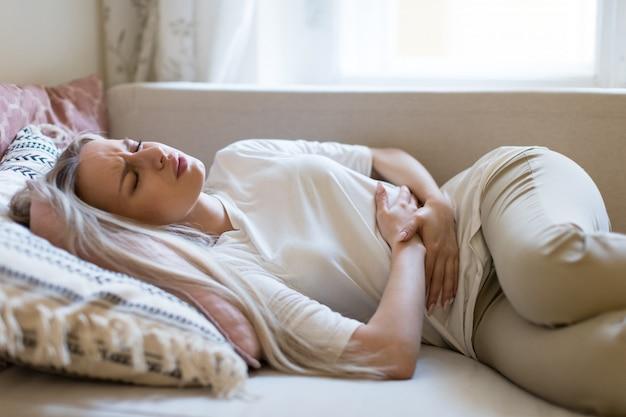 Femme souffrant de douleurs à l'estomac, ressentant des douleurs abdominales ou des crampes, allongée sur le canapé.