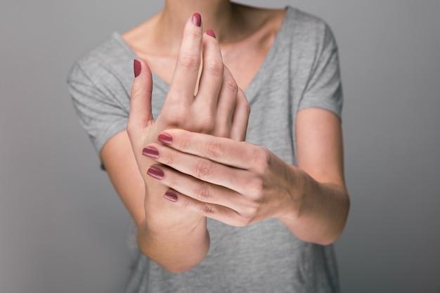 Femme souffrant de douleurs osseuses sur fond gris, concept avec grimace d'arthrite à la main dans la douleur