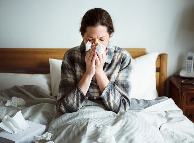 Une femme souffrant de la grippe au lit