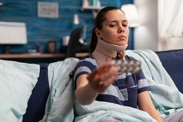 Femme souffrant de maladie et collier cervical en mousse sur un canapé prenant un traitement médical pour des douleurs au dos et au cou. adulte de race blanche avec contracture musculaire après une blessure physique dans un accident