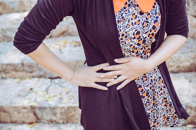 Femme souffrant de maux d'estomac en raison de gastrites ou de menstruations, signe de troubles gastriques.
