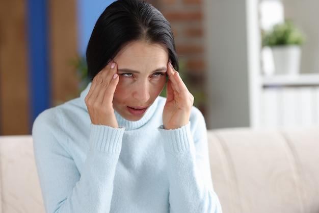 Une femme souffrant de maux de tête tient les mains aux tempes alors qu'elle est assise sur un canapé. symptômes de la migraine à la tête