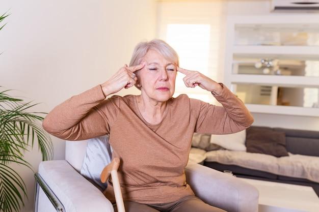 Femme souffrant de stress ou de maux de tête grimaçant de douleur.