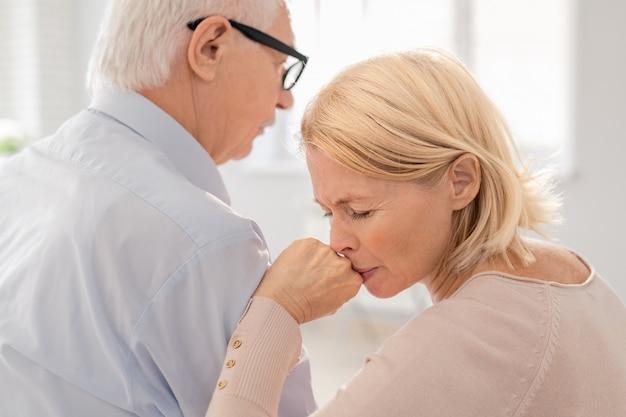 Femme souffrante blonde âgée s'appuyant sur l'épaule de son ami ou camarade de groupe lors d'une séance de psychothérapie