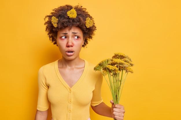 Une femme souffre d'une réaction allergique à une plante à fleurs a un aspect malsain une rougeur des yeux tient des fleurs sauvages isolées sur du jaune