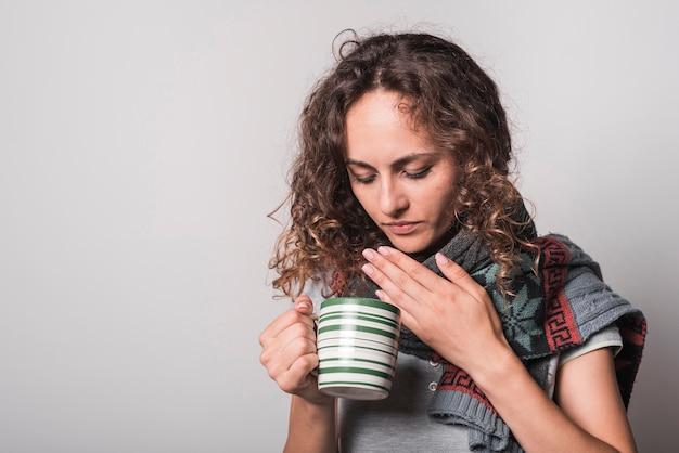 Femme, souffrir, froid, tenue, café, tasse, contre, fond gris