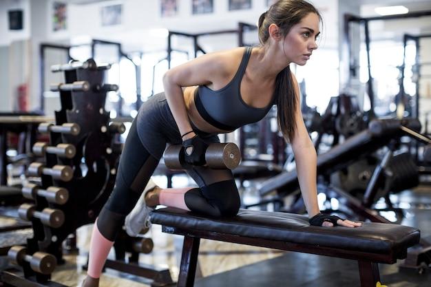 Femme soulevant des haltères dans la salle de gym
