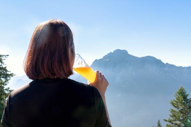 Femme soulevant un verre de bière et buvant de la bière en fût.