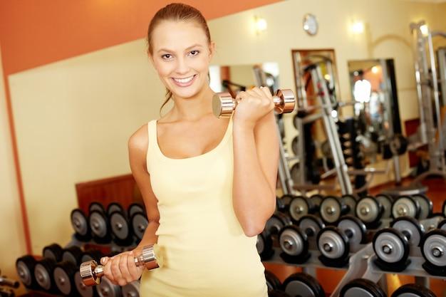 Femme soulever des poids à la salle de gym