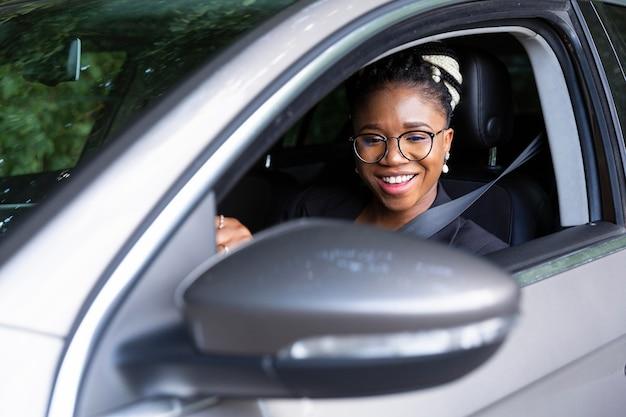 Femme souriant au volant de sa voiture personnelle