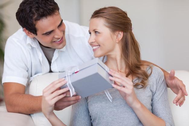 Femme souriant joyeusement du cadeau qu'elle vient de recevoir de son petit ami