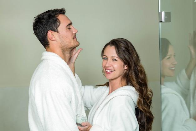 Femme souriant tout en appliquant une crème hydratante sur le visage de l'homme