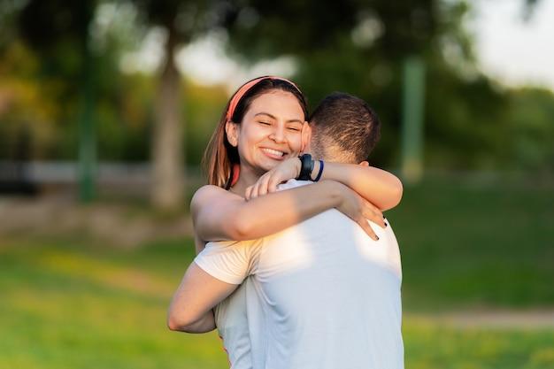 Femme souriant tout en serrant une femme dans un parc