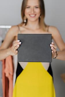 Femme souriante affichant une boîte minimale noire