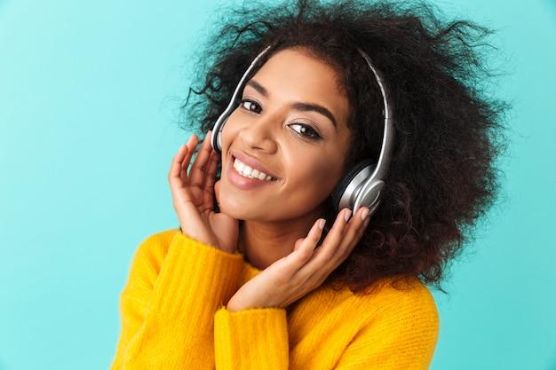 Femme souriante afro-américaine en chemise jaune, écouter de la musique via des écouteurs sans fil, isolé sur mur bleu
