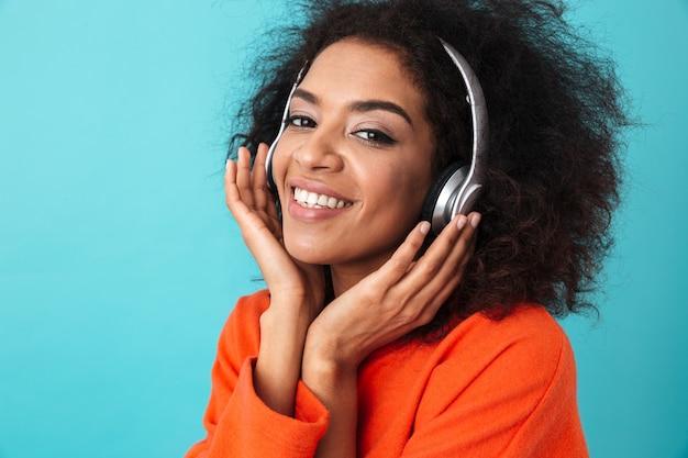 Femme souriante afro-américaine en chemise orange, écouter de la musique via des écouteurs sans fil, isolé sur mur bleu