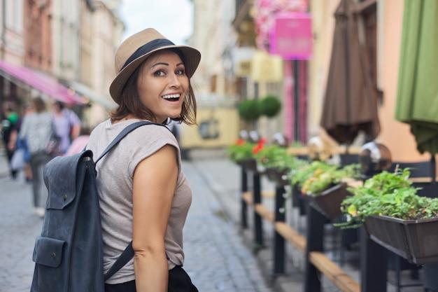 Femme souriante d'âge moyen en chapeau voyageant dans la ville touristique