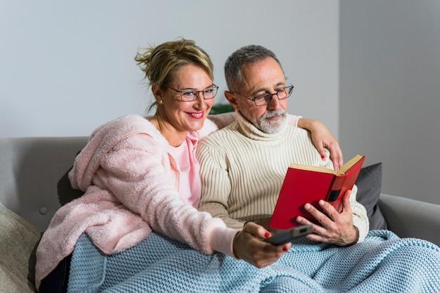 Une femme souriante âgée avec télécommande en regardant la télévision et un homme lisant un livre sur le canapé
