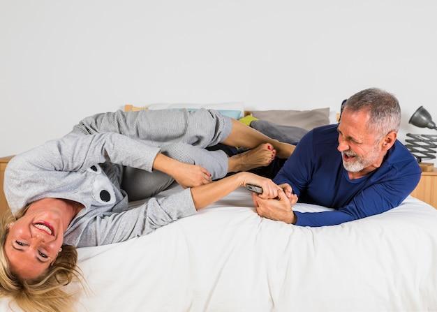 Femme souriante âgée voulant prendre la télécommande d'un homme les mains sur le lit