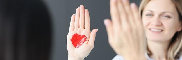 Femme souriante agitant sa main avec un coeur rouge dessiné réunions romantiques et concept de rencontres