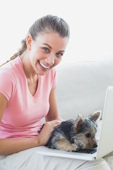 Femme souriante à l'aide d'un ordinateur portable avec son yorkshire terrier