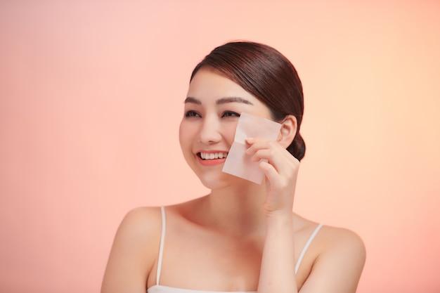 Femme souriante à l'aide d'un portrait de papier buvard à l'huile pour le visage.