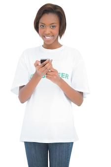 Femme souriante à l'aide de son téléphone portable